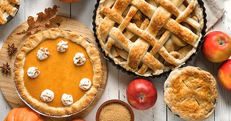 Pumpkin pie, apple pie, and apples overhead view still life.
